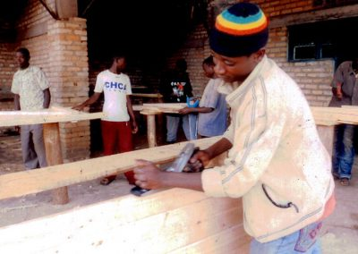 A student prepares the wood for one of the desks.