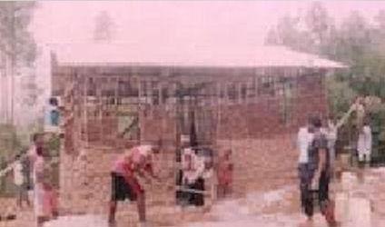 Schoolchildren help with the building of walls for Sixbert's house