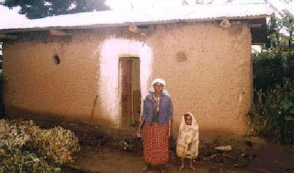 Xaverine with one of her children in front of the house after the roof has been replaced